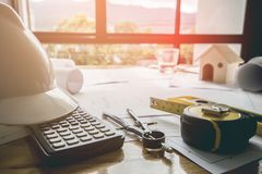 Concept architects, equipment architects On the desk with a blueprint in the office, Vintage, Sunset ligth. Selective Focus royalty free stock photos