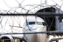 Concept of arresting terrorists on hijacked plane or other aviation incident. Airport security zone. Blurred aircraft. Behind a barbed wire fence royalty free stock image