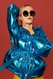 Concept art image of slim blonde girl in studio, wearing blue down jacket, posing on camera. Concept art image of slim blonde girl in studio, wearing blue down royalty free stock image