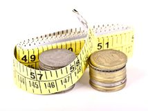 Concept art measuring the money. A concept art showing stack of coins with a measuring tape stock photography