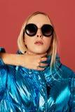 Concept art image of slim blonde girl in studio, wearing blue down jacket, posing on camera. Concept art photo shot of slim blonde girl in studio, wearing blue stock image