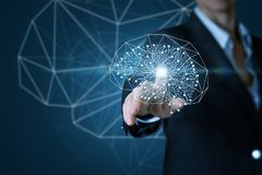 The concept is the artificial intellect. A businessman is touching a digital brain model consisting of wireless connections with a chip inside. The concept is stock images