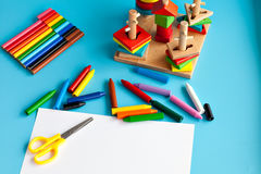The concept of the artistic activity of the child. Album for drawing and colored pencils on a blue background. toys for Stock Photos