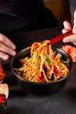 Concept of Asian cuisine. The girl is holding Japanese chopsticks in her hand and eating Chinese noodles from a black plate royalty free stock photo