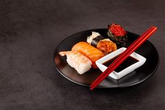 Concept of Asian cuisine. Japanese sushi with soy sauce on a black plate, on a black background. Red Chinese sticks copy space. Concept of Asian cuisine stock photos