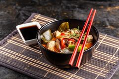 Concept of Asian cuisine. Thai soup Tom yam of chicken broth and coconut milk, mushrooms, chicken, chilli peppers, and vegetables. Japanese dish in black. Top stock photography