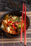 Concept of Asian cuisine. Thai soup Tom yam of chicken broth and coconut milk, mushrooms, chicken, chilli peppers, and vegetables. Japanese dish in black. Top royalty free stock photography