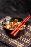 Concept of Asian cuisine. Thai soup Tom yam of chicken broth and coconut milk, mushrooms, chicken, chilli peppers, and vegetables. Japanese dish in black. Top stock images