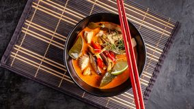 Concept of Asian cuisine. Thai soup Tom yam of chicken broth and coconut milk, mushrooms, chicken, chilli peppers, and vegetables. Japanese dish in black. Top stock photo