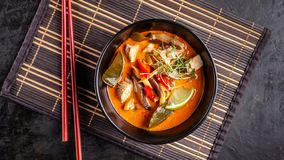 Concept of Asian cuisine. Thai soup Tom yam of chicken broth and coconut milk, mushrooms, chicken, chilli peppers, and vegetables. Japanese dish in black. Top stock image