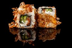 Concept of Asian cuisine. Two rolls of sushi with different fillings on a black background with the age for a Japanese menu. For a cafe, restaurant, sushi bar royalty free stock image