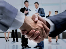 Concept of assistance in drafting business - friendly handshake. Closeup of handshake of businessmen on background of employees Stock Photo