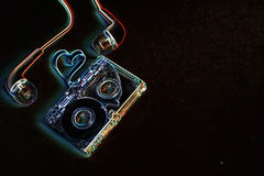 Concept audio tape on a blue rock. Audiocassette retro music and film of her folded in the shape of a heart and headphones Stock Photos