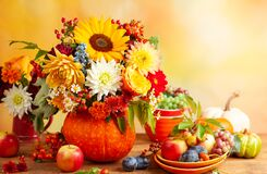 Concept of autumn festive decoration for Thanksgiving day. Autumn bouquet of flowers and berries in a pumpkin on a table,