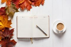 The concept of autumn mood. Morning coffee, diary and colored maple leaves. Top view.  Royalty Free Stock Image