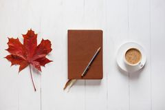 The concept of autumn mood. Morning coffee, diary and colored maple leaves. Top view.  Royalty Free Stock Photo