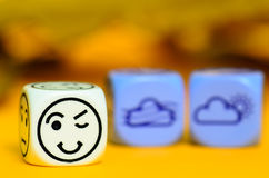 Concept of autumn weather - emoticon and weather dice on orange Stock Photos