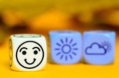 Concept of autumn weather - emoticon and weather dice on orange Stock Images