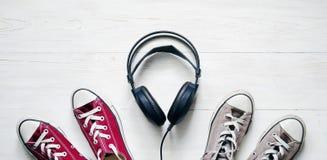 Concept avec le claret et les écouteurs d'espadrille et noirs gris étendus Image stock