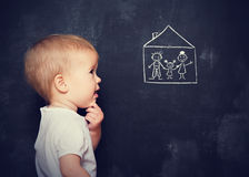 Concept baby looks at board, which is drawn family and home Royalty Free Stock Image