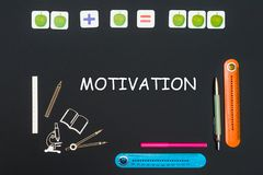 Above stationery supplies and text motivation on blackboard. Concept back to school, above stationery supplies and text motivation on black backboard Royalty Free Stock Image