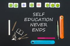 Above stationery supplies and text self education never ends on blackboard. Concept back to school, above stationery supplies and text self education never ends Royalty Free Stock Photography