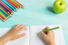Concept back to school.School supplies, colored pencils, pen with empty notebook on blue wooden background. Girl holding