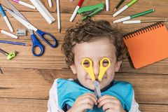 Child surrounded by school supplies royalty free stock photos