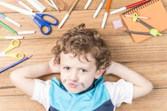 Child surrounded by school supplies. Concept back to school. Child lying on wooden boards, surrounded by school supplies and putting some clips like a mustache stock images