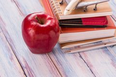 Concept of back to school. Pile of books and red apple. On the desk over the blur background Royalty Free Stock Photos