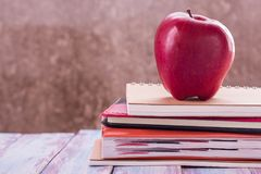 Concept of back to school. Pile of books and red apple. On the desk over the blur background Stock Photography