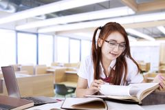 Pretty teenage student studying in class. Concept of Back to School. Pretty teenage student studying in the classroom while wearing glasses and reading books Royalty Free Stock Photos