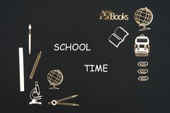 School supplies placed on black background with text school time. Concept back to school, text school time with school supplies chipboard miniatures placed on Royalty Free Stock Photo