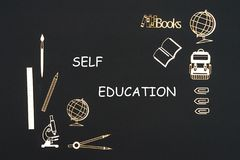 School supplies placed on black background with text self education. Concept back to school, text self education with school supplies chipboard miniatures placed Royalty Free Stock Photography