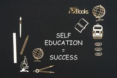 School supplies placed on black background with text self education success. Concept back to school, text self education success with school supplies chipboard Royalty Free Stock Photos