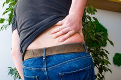 Concept of backaches, back pain or manifestations or symptoms of radiculopathy. Man grabbed with Palm over lumbar region on back,. Indicating localization of stock photo