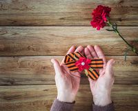 Concept background of May 9 russian holiday Victory Day. Old woman holding in hands a red carnation and St. George`s ribbon. Flat stock image