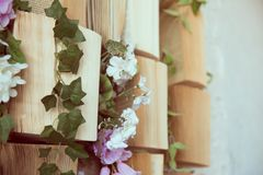 Concept background opened books on the wall and flowers of artificial purple and white.  stock images