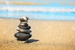 Concept of balance and harmony. Rocks on the coast of the Sea in the nature. Stones pyramid on sand symbolizing zen, harmony, balance. Ocean in the background Royalty Free Stock Photos