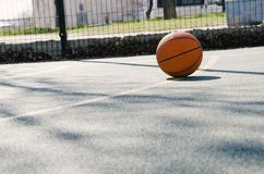 Concept of basketball game at the small sport ground outdoor.Sport court and ball outside. School sport ground outdoor.Basketball ball on the empty sport court stock images
