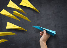 Concept - Be Different. Concept - Being different. A man about to throw a paper plane in a different direction to everyone else Stock Image