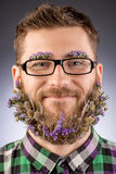 Concept beard. Handsome smiling young man in glasses and a beard of flowers Royalty Free Stock Photos