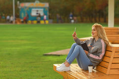 Concept of beautiful young woman having an idea. Trendy woman in sitting on the bench in city park. Royalty Free Stock Photo