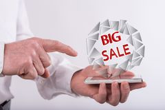 Concept of big sale. Big sale concept above a smartphone held by a man Royalty Free Stock Photos