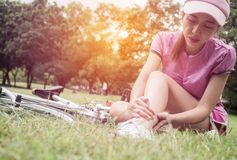 Concept bike accident, Woman with pain in knee joints after biking on bicycle in park. Ankle hurts after bike fall.  royalty free stock photography