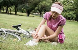 Concept bike accident, Woman with pain in knee joints after biking on bicycle in park. Ankle hurts after bike fall.  stock image