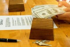 Concept, billet de banque à disposition avec la maison modèle et clé d'immobiliers dessus Image stock