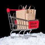 Concept of black friday shopping trolley with paper bags in snow. Is isolated on black background Royalty Free Stock Photography