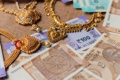 Concept of black money, IT raid, confiscated or unaccounted Money showing Indian currency notes with jewelry royalty free stock image