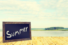 Concept with blackboard and summer calm landscape Stock Image